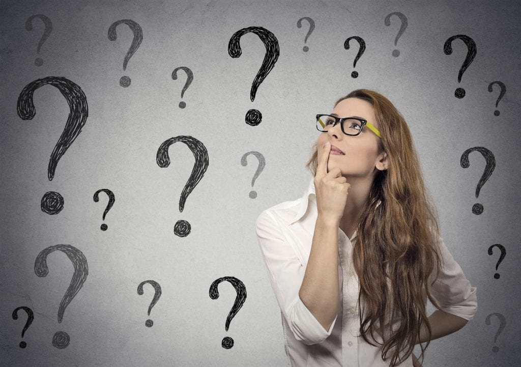 Business woman with glasses looking up at many question marks
